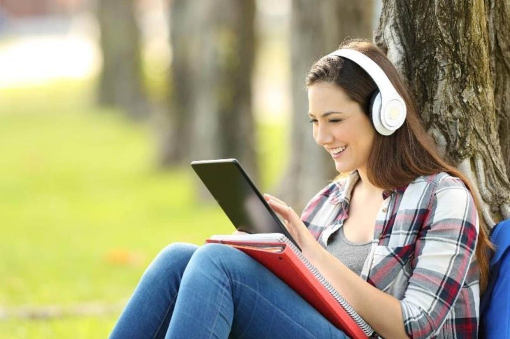 a female student with headphones on is working on a tablet while she sits outside