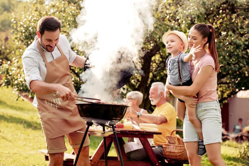 a family is outdoors in the Texas summer heat grilling while the rest of their family sits around a picnic table