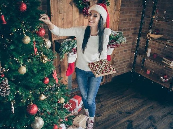 a woman wearing a santa hat is holding a box of ornaments and decorating her tree with those ornaments