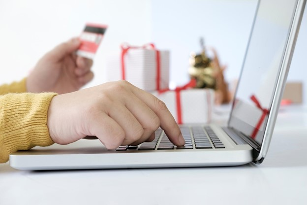 a person sits at a computer with their credit card in one hand as they type in the number with their other hand
