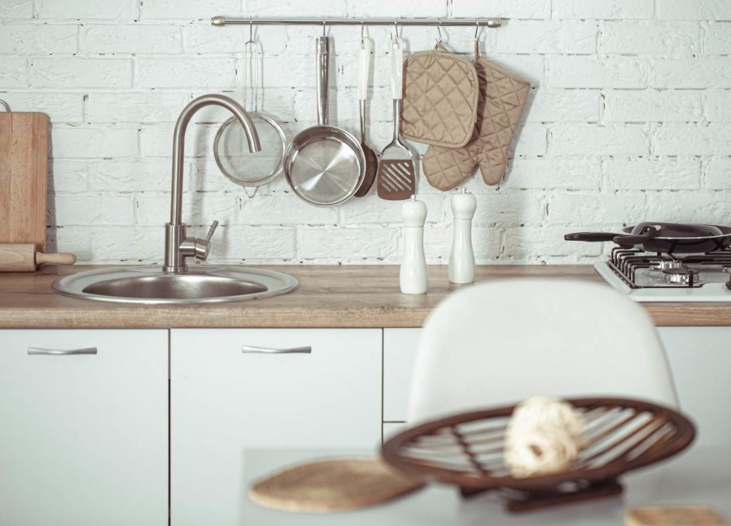 a variety of kitchen tools are hanging on a wall mount in an apartment