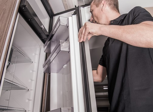 A man checking the refrigerator in his RV