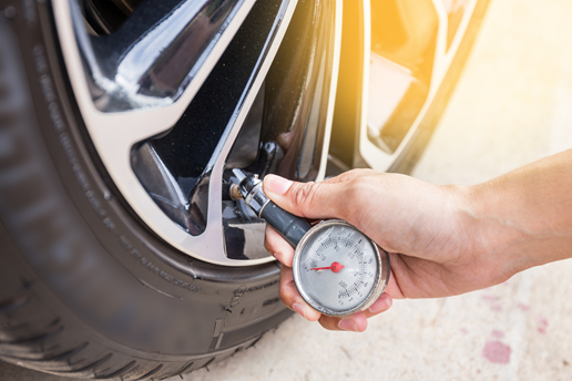 A person checking the tire pressure of a tire with a tire gauge