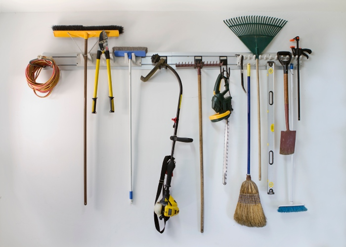 a hanging rack filled with gardening and outdoor tools