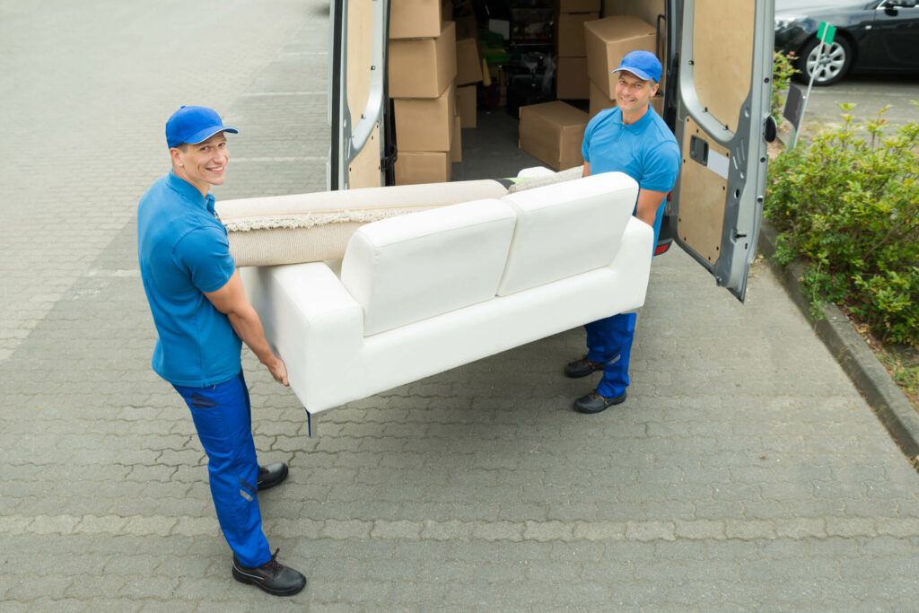 two men moving a small couch from a moving van
