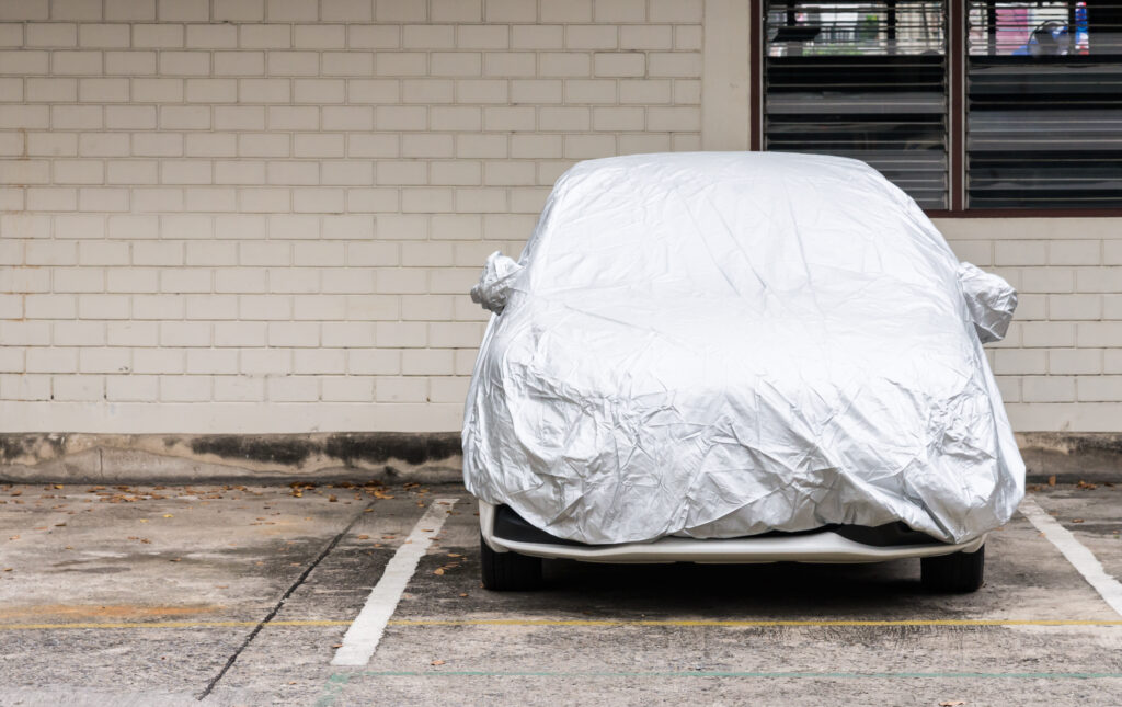 Parked vehicle with silver vehicle cover on top