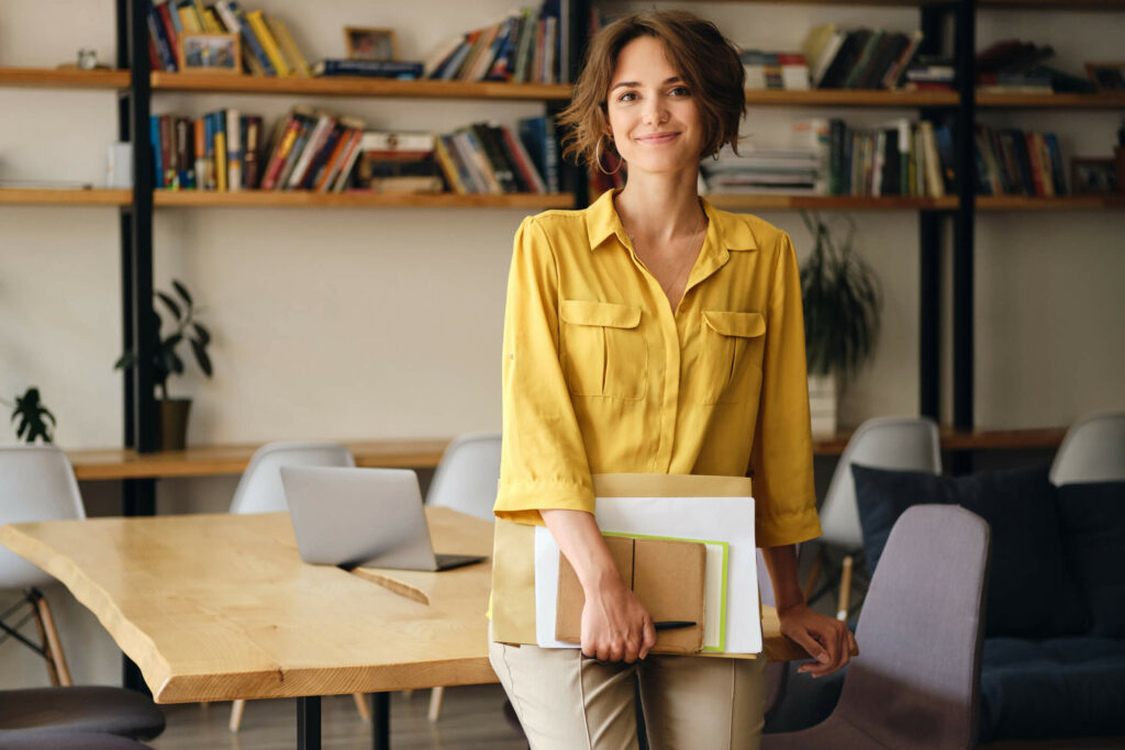 Smiling woman leaning against a table while holding papers.